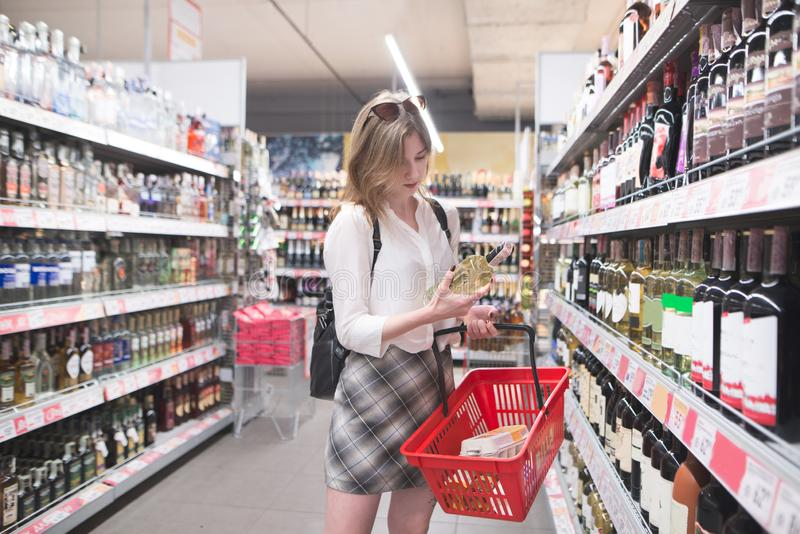 Woman is in the alcohol department of a supermarket with a bottle of wine in her hands and looks at the label. Young woman is in the alcohol department of a royalty free stock photos