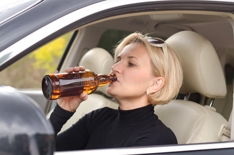Woman alcoholic drinking as she drives the car royalty free stock photo