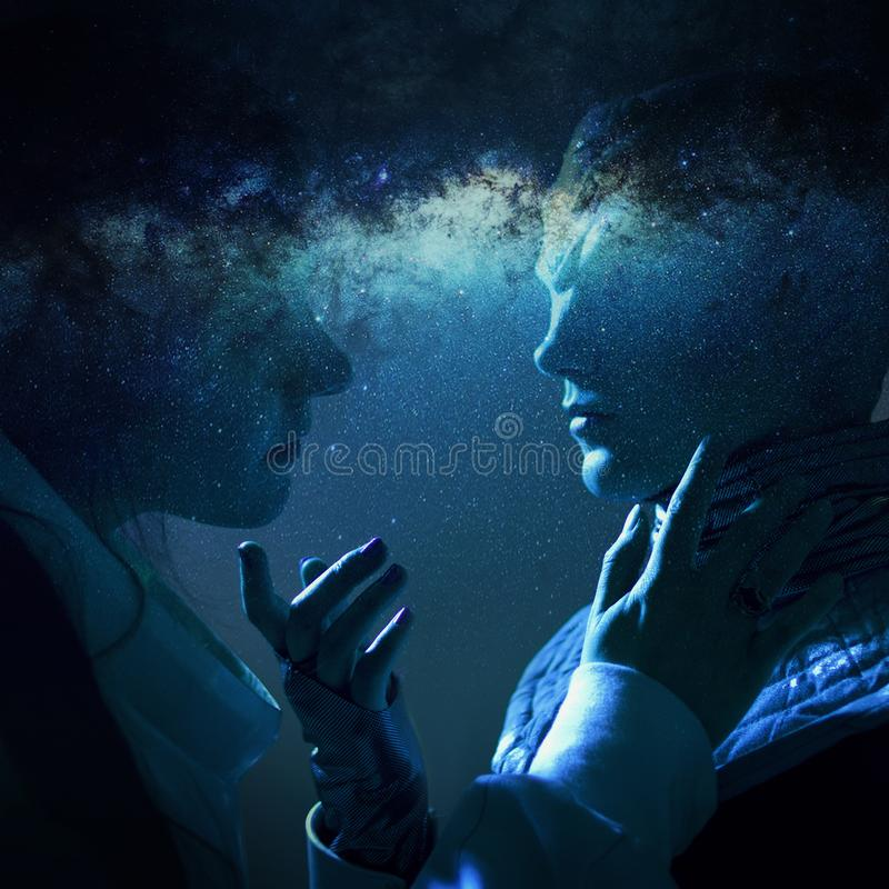 Woman and an alien look at each other. Contact with other civilizations. Space and galaxy stock photography