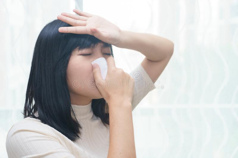 Woman with allergy or cold sneezing into napkin in her room - he stock photo