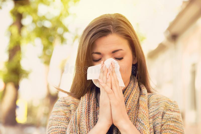 Woman with allergy symptoms blowing nose. Standing on a street royalty free stock photography