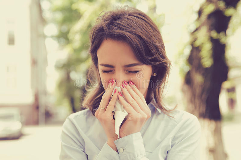 Woman with allergy symptoms blowing nose. Young woman with allergy symptoms blowing nose royalty free stock images
