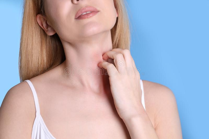 Woman with allergy symptoms scratching neck on color background. Closeup stock photos