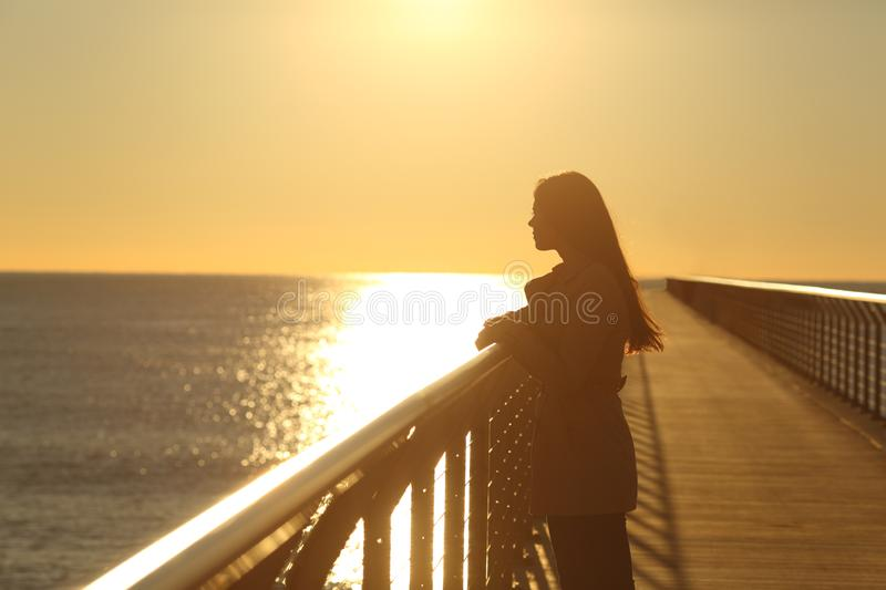 Woman alone contemplating ocean at sunset stock photo
