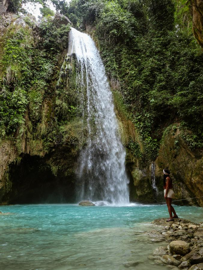 Woman couple alone in deep forest waterfall, inambakan falls in Cebu Island in Philppines. Woman alone in deep forest waterfall from mountain gorge at hidden stock photos