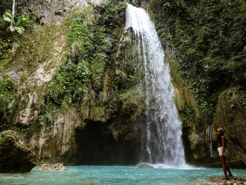 Woman couple alone in deep forest waterfall, inambakan falls in Cebu Island in Philppines. Woman alone in deep forest waterfall from mountain gorge at hidden stock photography