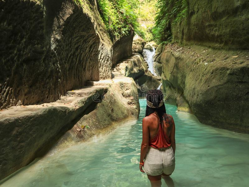 Woman alone on the green canyon in Dao Falls in Cebu Island, Philippines. Woman relaxing alone on the green canyon road at the middle of tropical jungle on the royalty free stock images