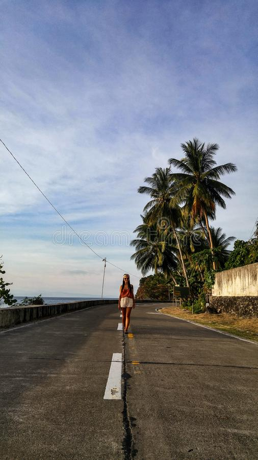 Woman alone at the road with palm trees in Cebu Island. Woman walking alone at the empty road with lots of palm trees in Cebu Island in Philippines royalty free stock photo