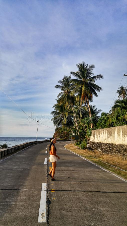 Woman alone at the road with palm trees in Cebu Island. Woman walking alone at the empty road with lots of palm trees in Cebu Island in Philippines stock photos