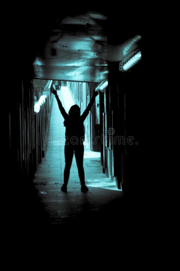 Silhouette of woman alone at the end of a tunnel royalty free stock photos
