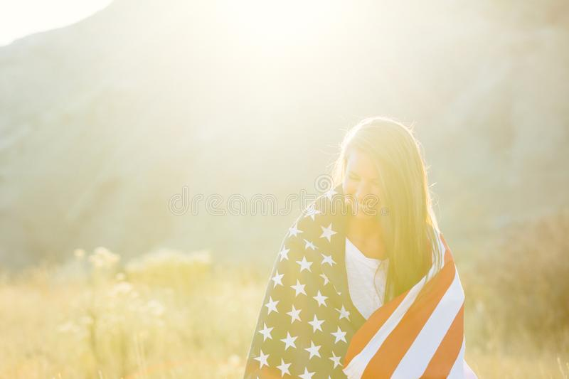 Woman with American Flag. An attractive young woman in a field with an American Flag royalty free stock images