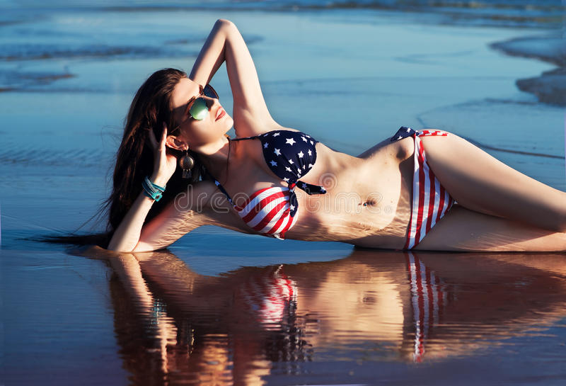 Woman in in american flag bikini in water, sea, waves. Fashion, sunglasses. Outdoor stock images