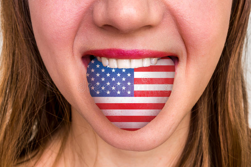 Woman with american flag on the tongue. Learning a foreign language royalty free stock photo