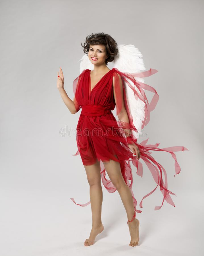 Woman Angel in Cupid Wings Costume, Happy Fashion Model in Red Dress, Beauty Girl. Over White Background royalty free stock photos