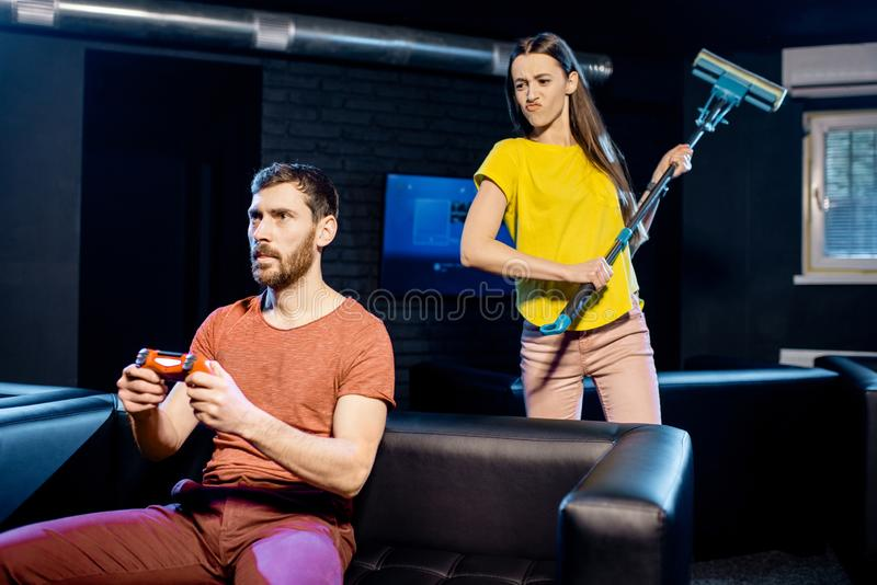 Woman angry at her boyfriend playing video games stock image