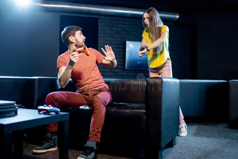 Woman angry at her boyfriend playing video games stock photo