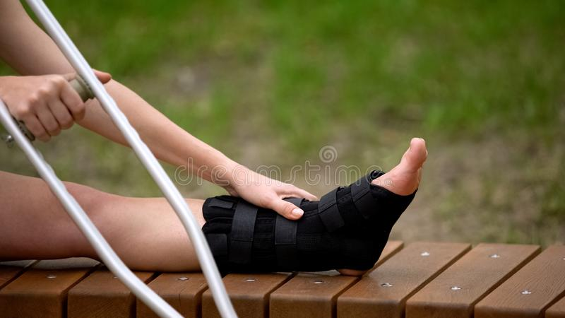Woman with ankle brace holding crutch sitting outdoors, trauma bandage, health stock photos