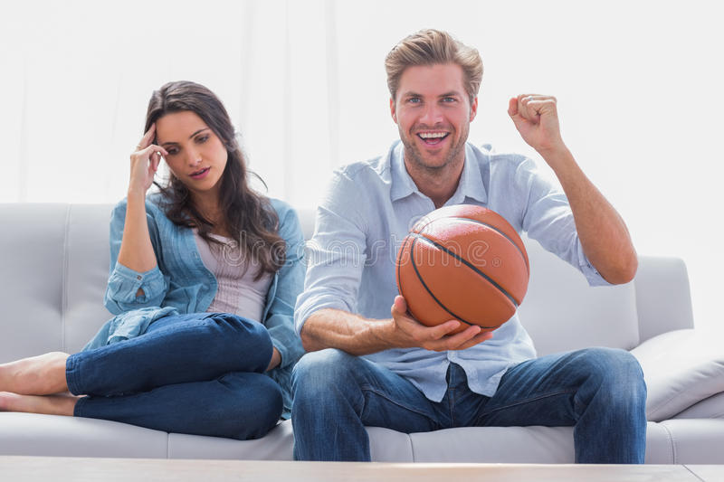 Woman annoyed by her partner watching basketball game. In the living room stock photo