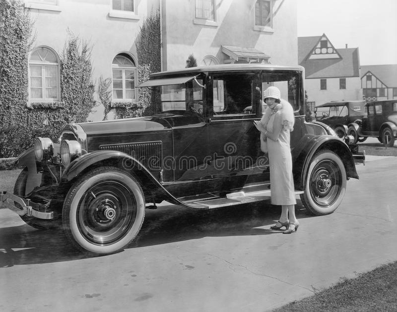 Woman with antique car outside large house royalty free stock photo