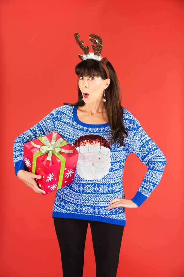 Woman in antlers tiara holding Christmas gift. Excited beautiful single woman in tacky knitted sweater and antlers tiara holding a large Christmas gift royalty free stock photos