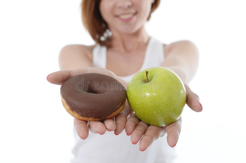 Woman with Apple and Chocolate Donut in Hands stock photo