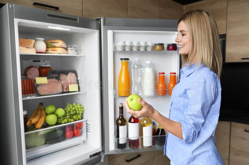 Woman with apple near refrigerator. In kitchen royalty free stock image
