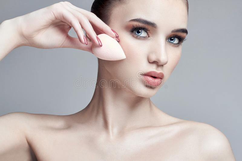 Woman applied with a sponge makeup on the face. Professional makeup with your hands. Care for the skin, natural cosmetics. Skincare products stock photo