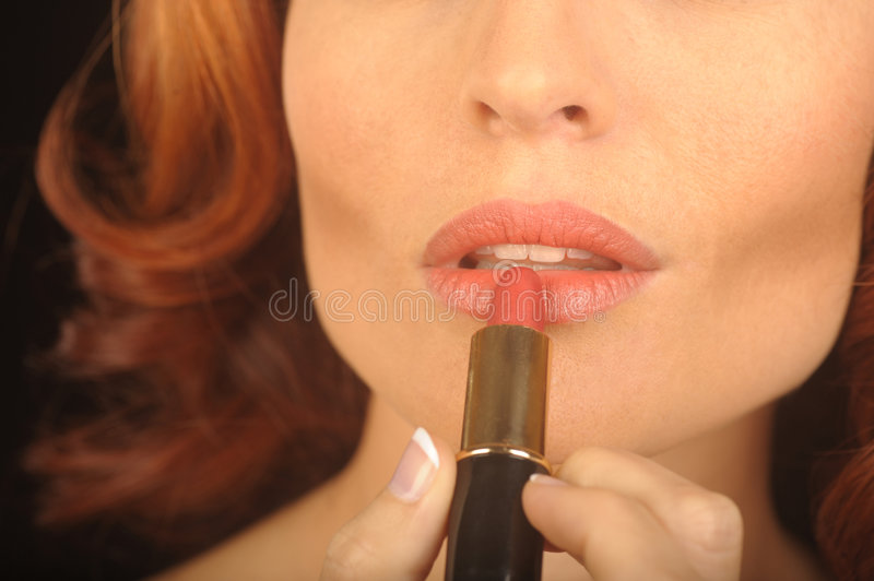 Woman Applies lipstick royalty free stock images
