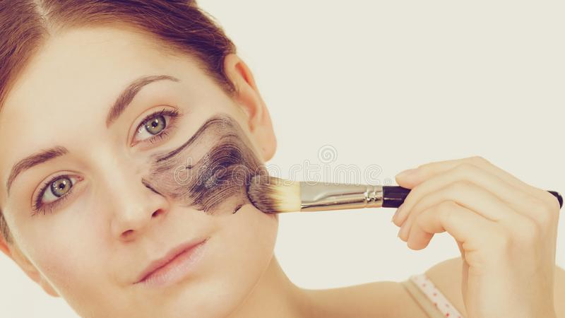 Woman apply black carbo mask to face. Woman being applying with brush clay carbo detox black mask to her face, on white. Girl taking care of oily skin complexion royalty free stock photo