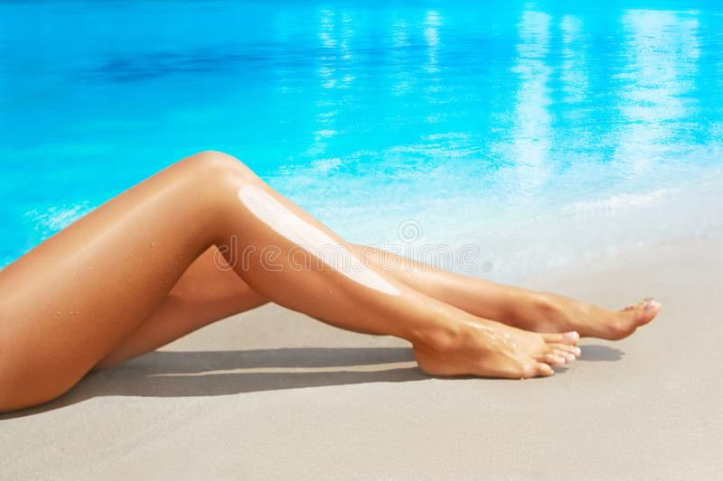 Woman apply sun protection cream on her smooth tanned legs. Sunscreen. stock images