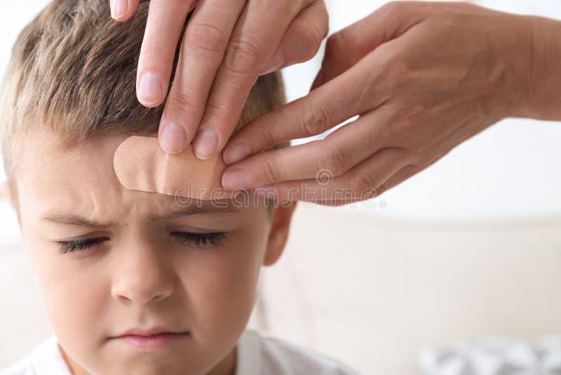 Woman applying adhesive bandage on boy`s forehead indoors. Closeup royalty free stock photography