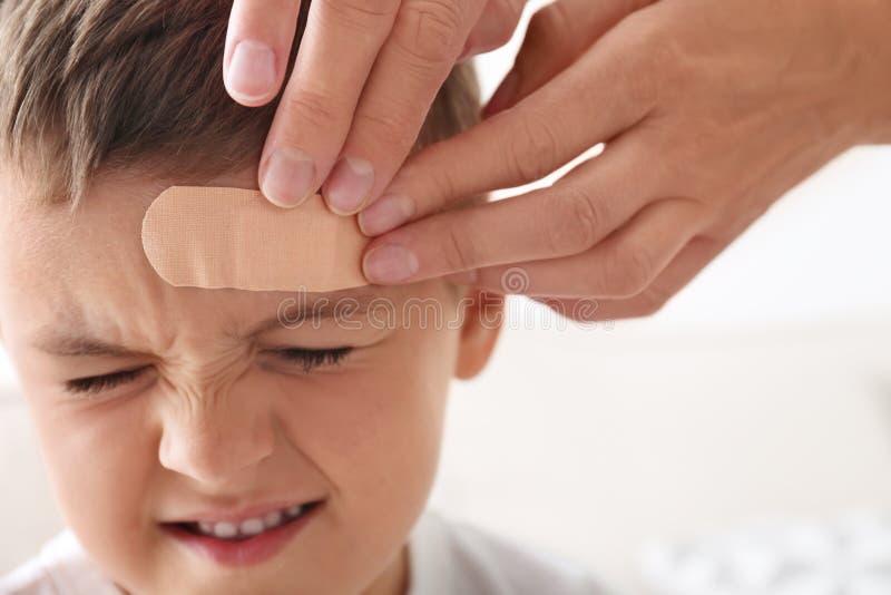 Woman applying adhesive bandage on boy`s forehead indoors. Closeup stock photo