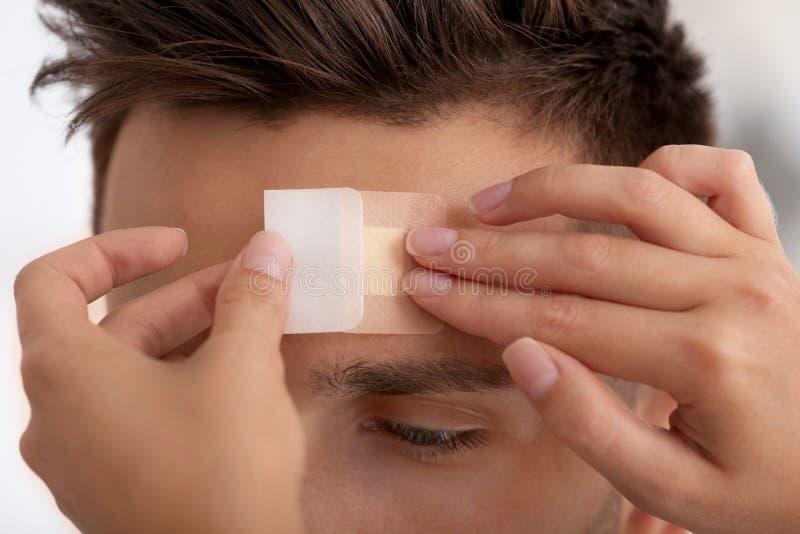Woman applying adhesive bandage on man`s forehead. Closeup view royalty free stock photos