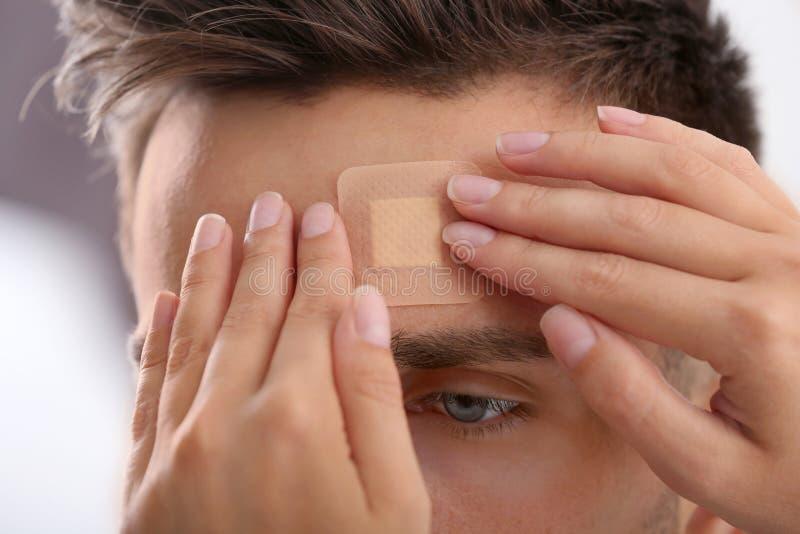 Woman applying adhesive bandage on man`s forehead. Closeup view royalty free stock photography