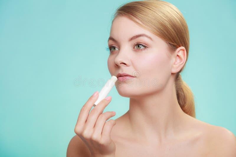 Woman applying balsam for lips. Female putting applying lip balm moisturizing balsam. Girl taking care of lips. Skincare royalty free stock photos