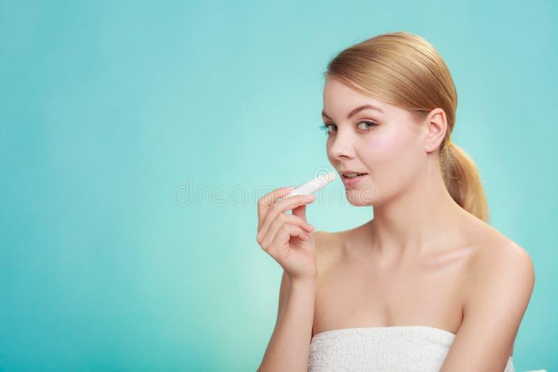 Woman applying balsam for lips. Female putting applying lip balm moisturizing balsam. Girl taking care of lips. Skincare stock image
