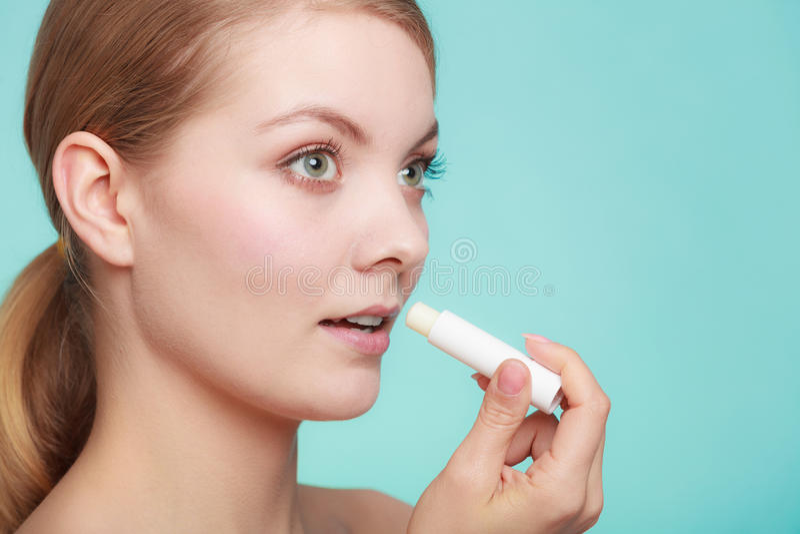 Woman applying balsam for lips. Female putting applying lip balm moisturizing balsam. Girl taking care of lips. Skincare stock images