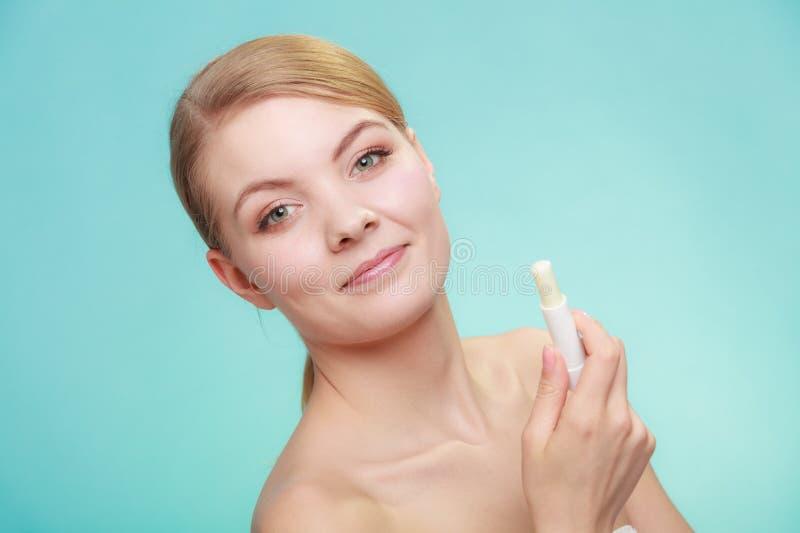 Woman applying balsam for lips. Female putting applying lip balm moisturizing balsam. Girl taking care of lips. Skincare royalty free stock photography