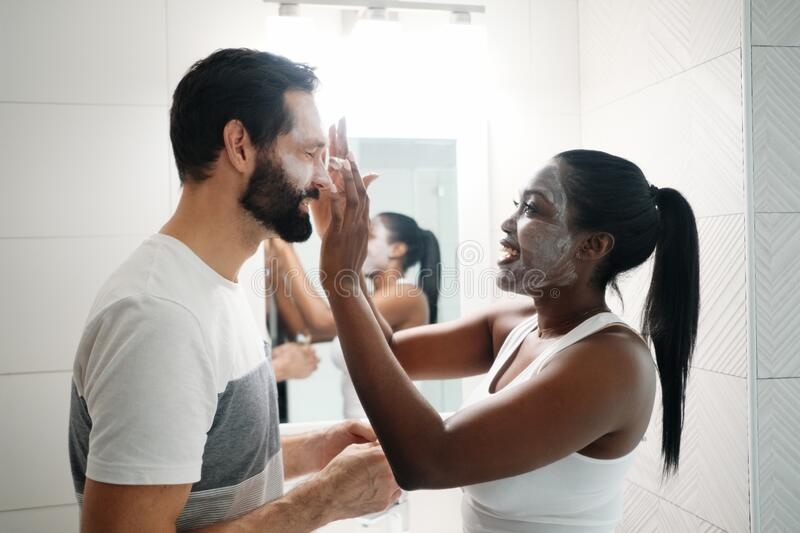 Woman Applying Beauty Mask And Skin Cleanser To Man royalty free stock photography