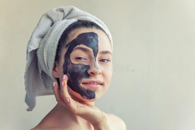 Woman applying black nourishing mask on face. Beauty portrait of woman in towel on head applying black nourishing mask on face, white background isolated royalty free stock images
