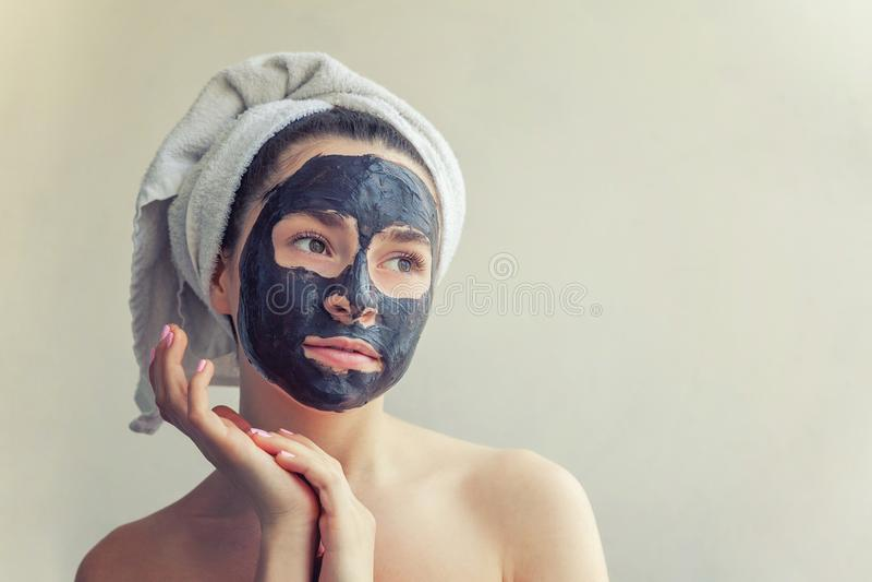 Woman applying black nourishing mask on face. Beauty portrait of woman in towel on head applying black nourishing mask on face, white background isolated royalty free stock photo