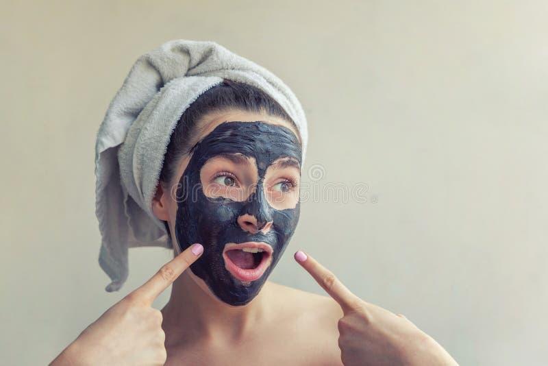 Woman applying black nourishing mask on face. Beauty portrait of woman in towel on head applying black nourishing mask on face, white background isolated stock photos