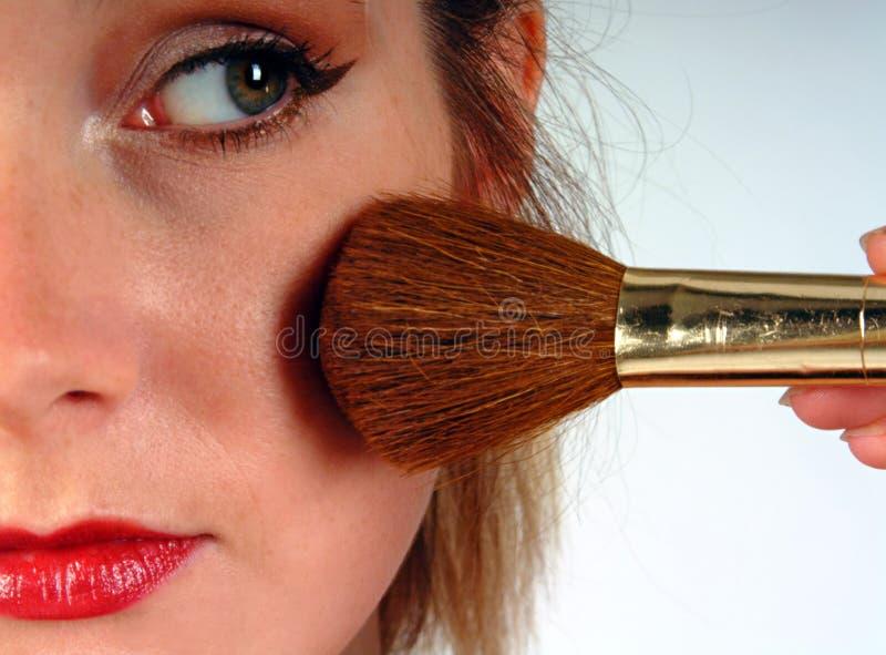 Woman applying blusher stock photography