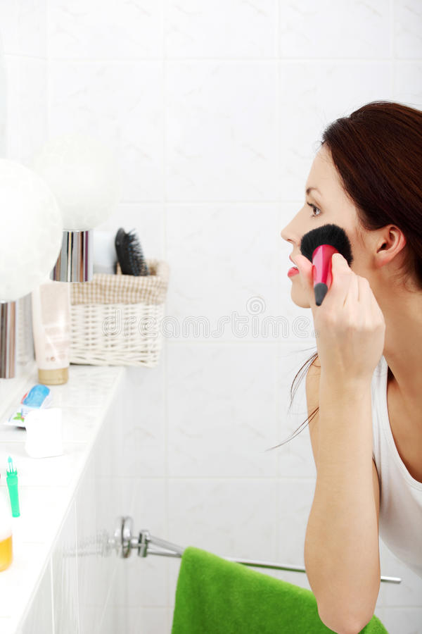 Woman applying blusher in her bathroom. royalty free stock photo