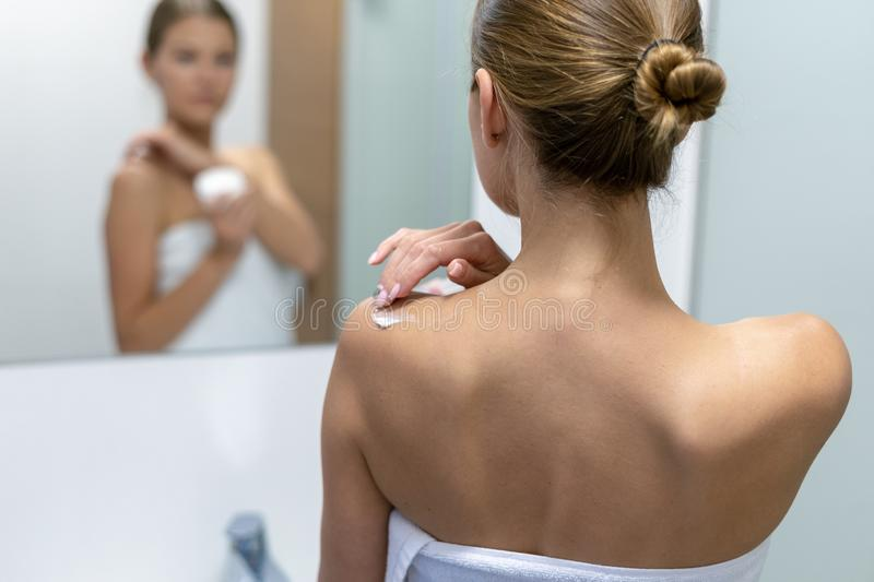 Woman applying body cream on shoulder in bathroom royalty free stock image