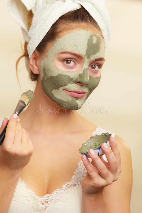 Woman applying with brush clay mud mask to her face. Skin care. Woman applying with brush clay mud mask to her face. Girl taking care of oily complexion. Beauty royalty free stock photo