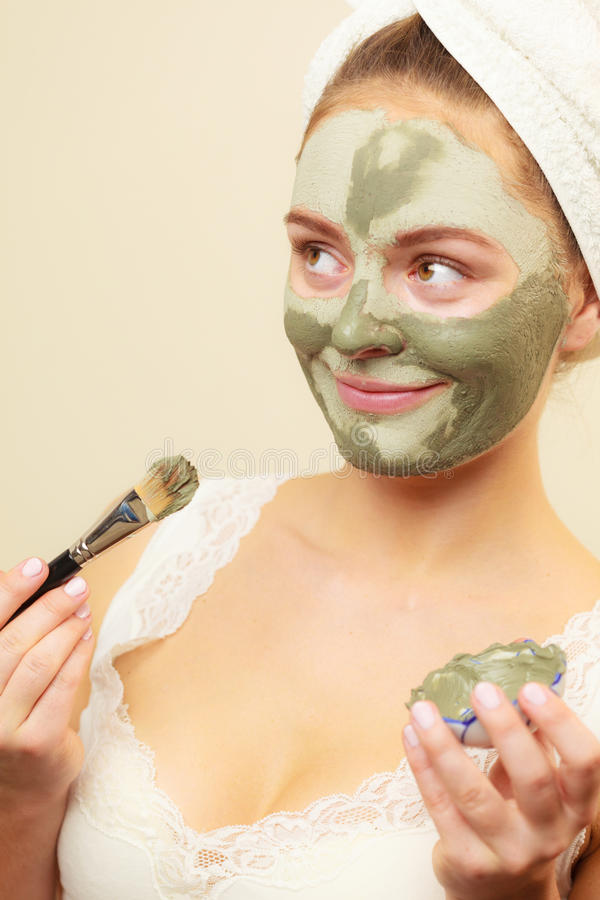 Woman applying with brush clay mud mask to her face. Skin care. Woman applying with brush clay mud mask to her face. Girl taking care of oily complexion. Beauty royalty free stock photography
