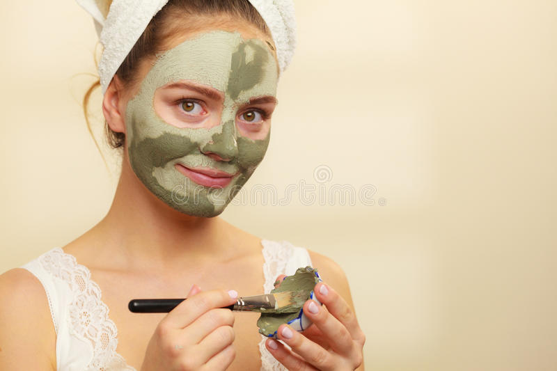 Woman applying with brush clay mud mask to her face. Skin care. Woman applying with brush clay mud mask to her face. Girl taking care of oily complexion. Beauty stock photo