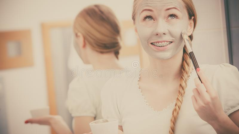 Woman applying with brush clay mud mask to her face. Skincare. Blonde woman in bathroom applying with brush gray clay mud mask to her face. Young lady taking stock photos