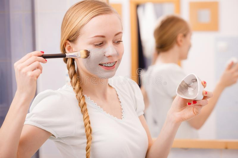 Woman applying with brush clay mud mask to her face. Skincare. Blonde woman in bathroom applying with brush gray clay mud mask to her face. Young lady taking stock images